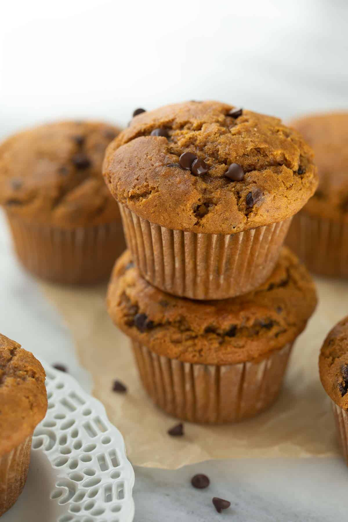 2 pumpkin muffins stacked on brown parchment paper with chocolate chips