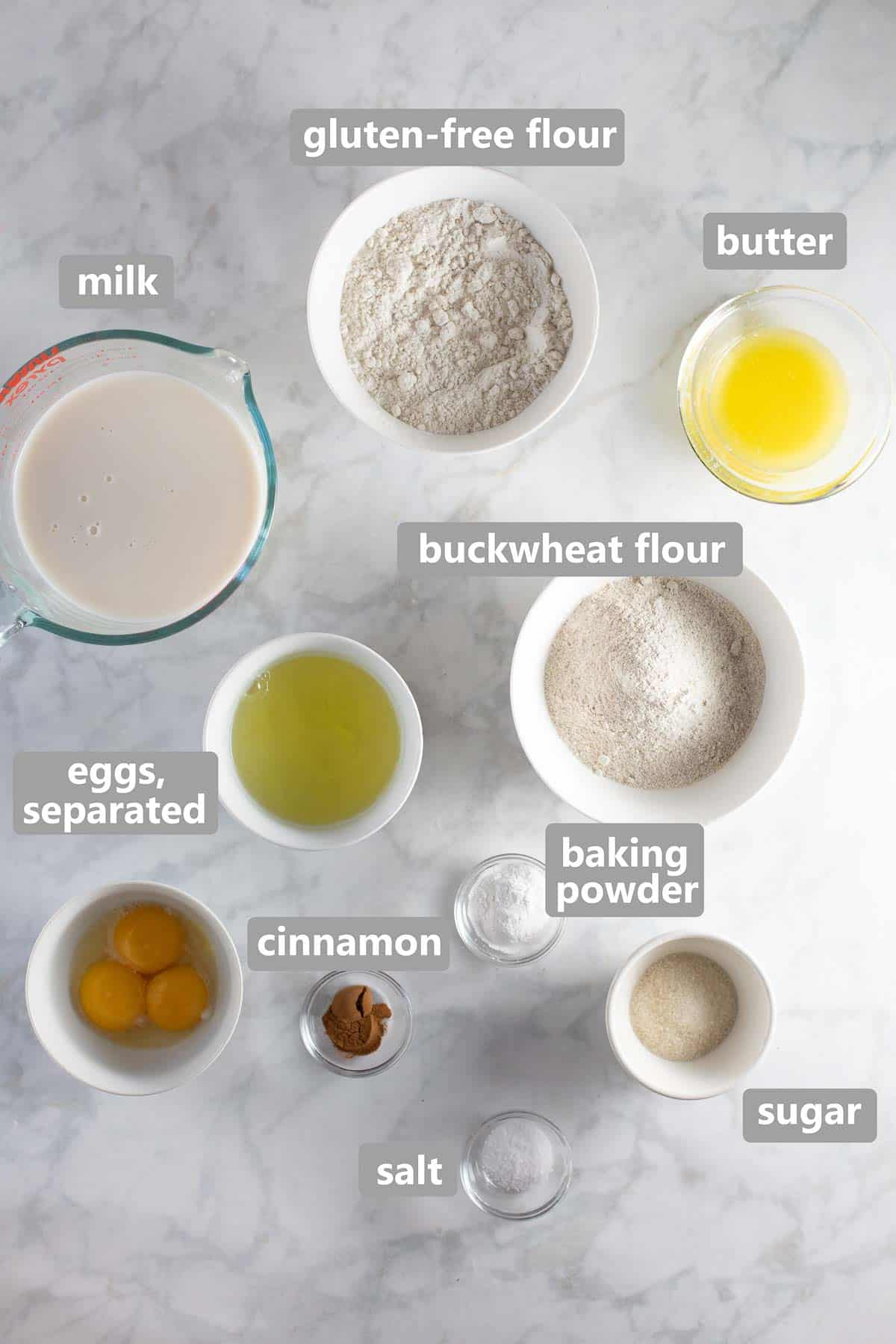 overhead shot of ingredients needed to make buckwheat pancakes set out in bowls