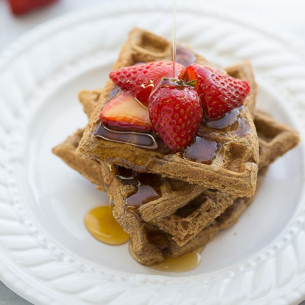 buckwheat waffles stacked on white plate with syrup and berries