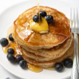 stack of gluten-free pancakes on white plate topped with blueberries and maple syrup
