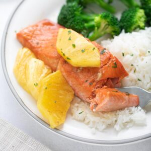 pineapple salmon on white rice with broccoli on white plate