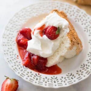 shot of gluten-free angel food cake on white plate topped with strawberry sauce