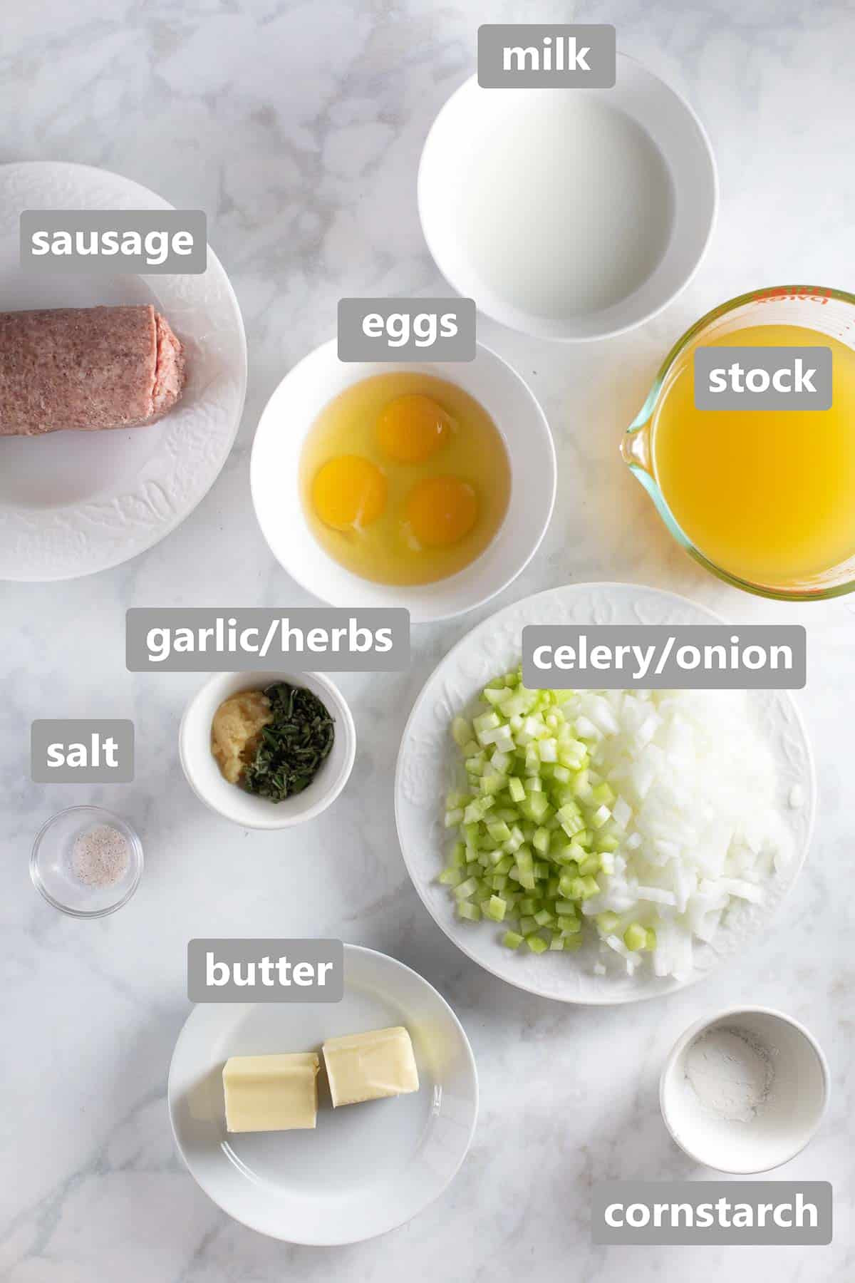 ingredients to make the sausage stuffing set out on marble background