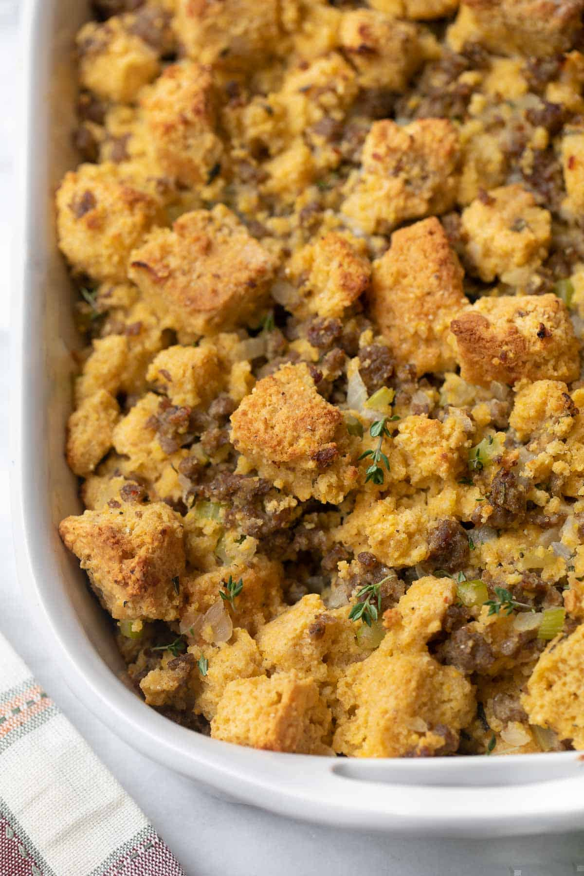 close up of gluten-free cornbread stuffing in white casserole dish with plaid napkin