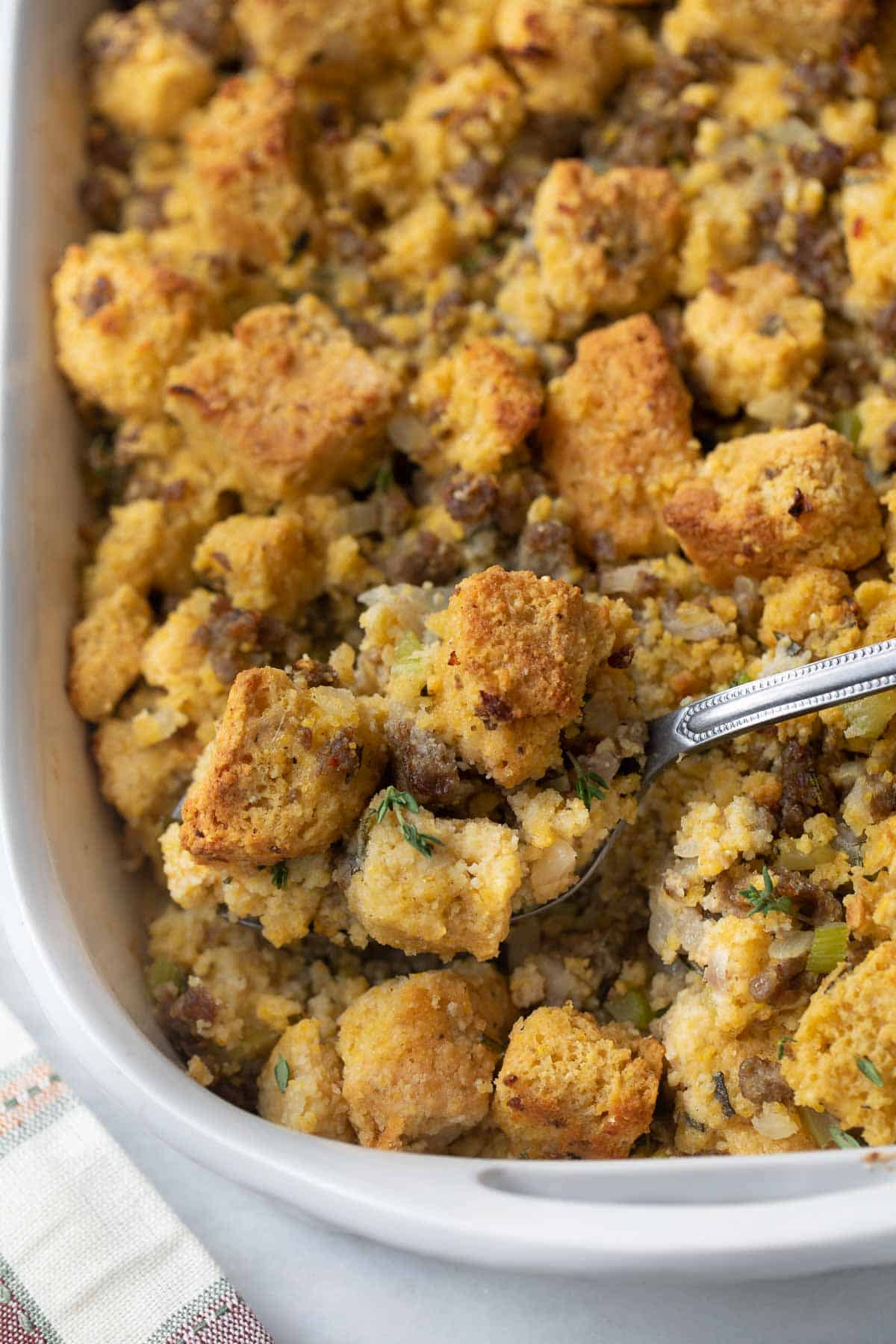 silver spoon scooping gluten-free cornbread sausage stuffing out of white casserole dish