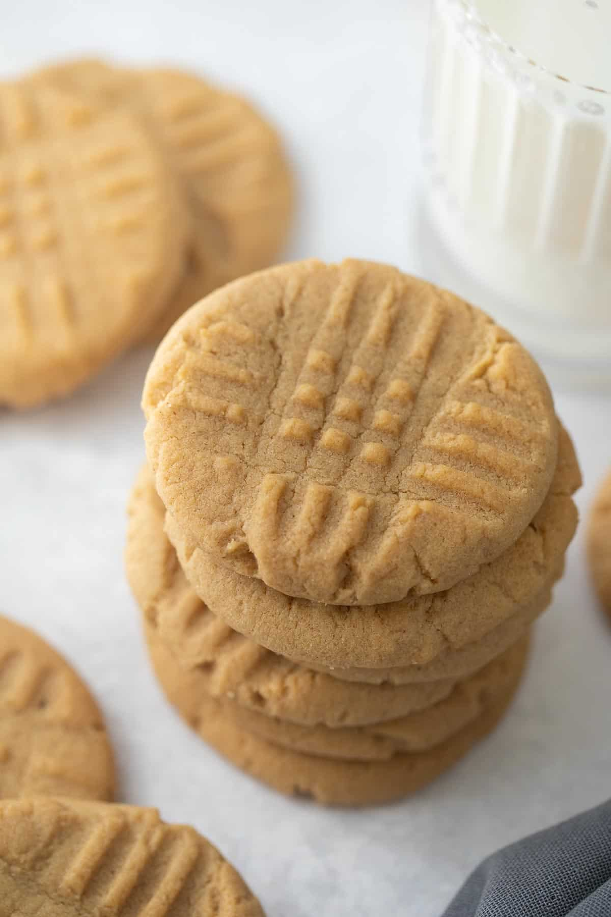cookies stacked on top of each other on gray background with napkin and glass of milk