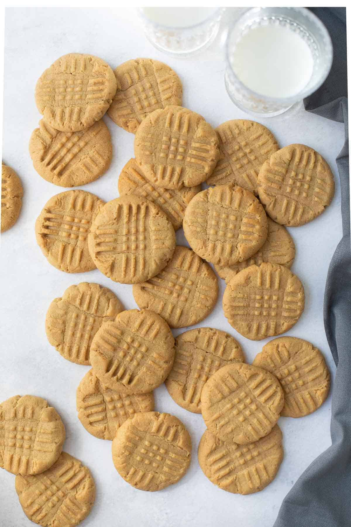 overhead shot of all the cookies on marble background with gray napkin and glass of milk
