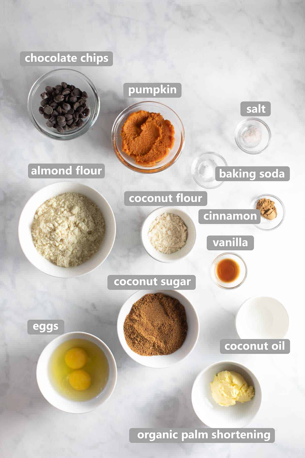ingredients to make pumpkin cookies in bowls on marble background