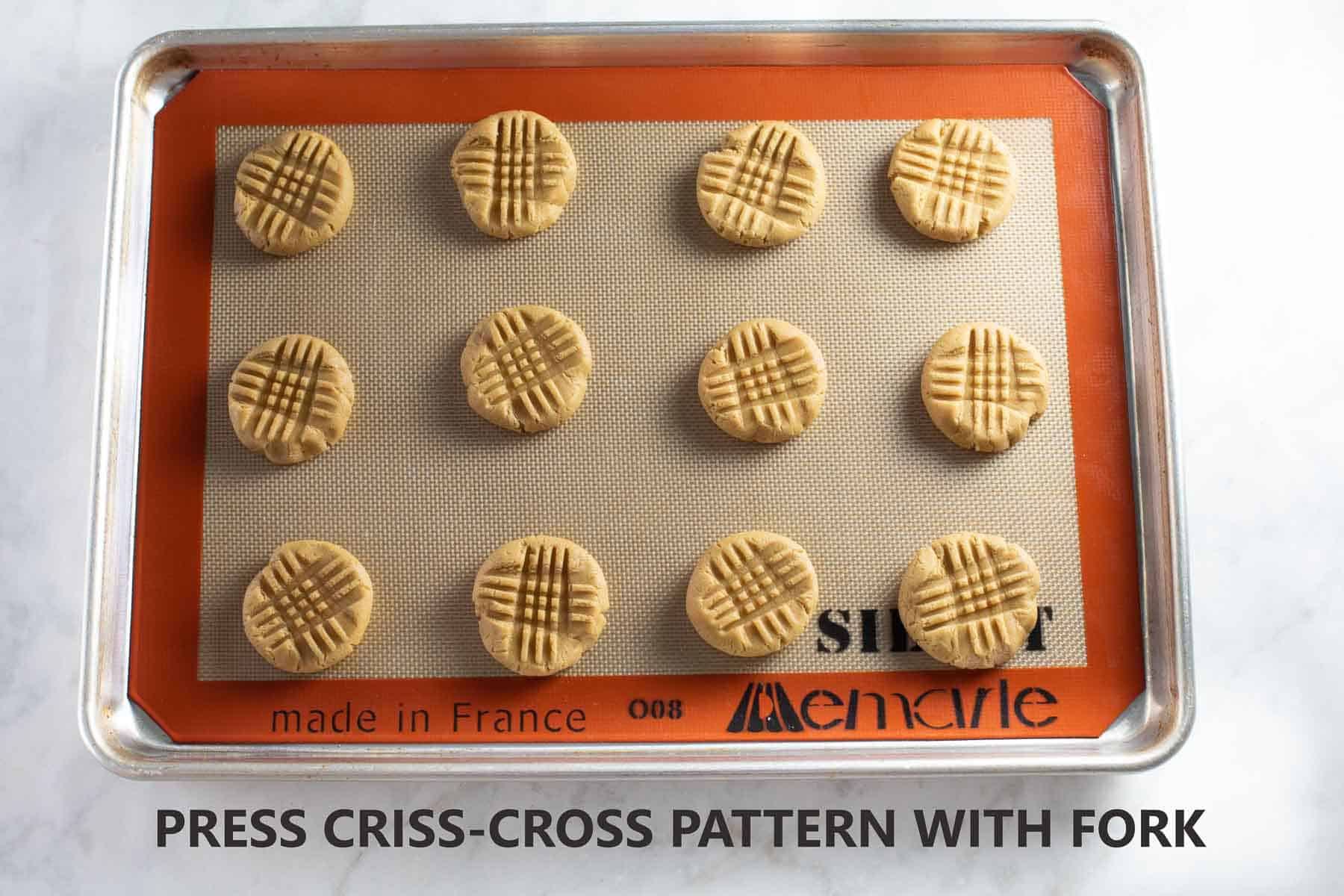 cookies on baking pan with criss-cross pattern made with fork