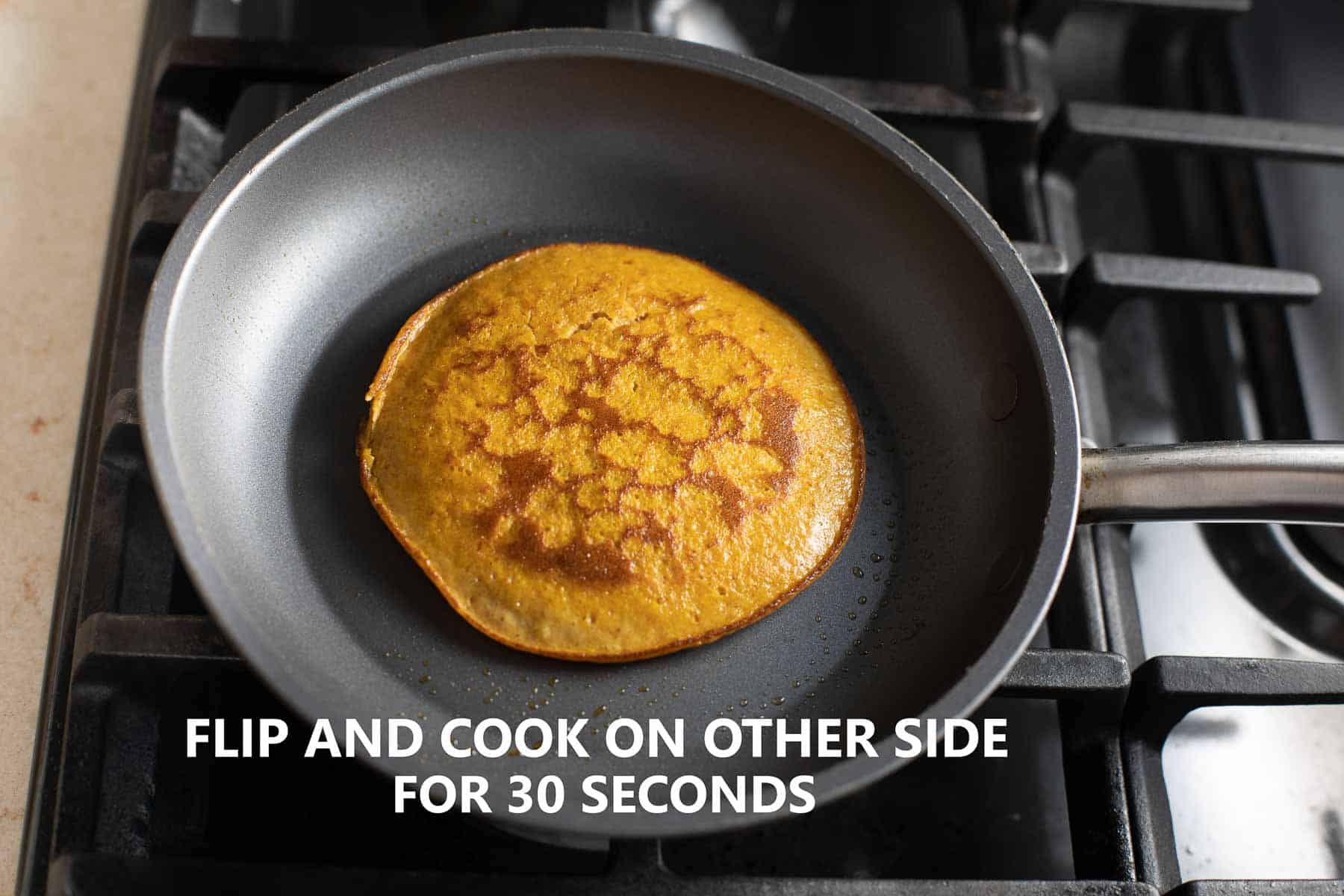flipped pumpkin pancake cooking in black nonstick pan