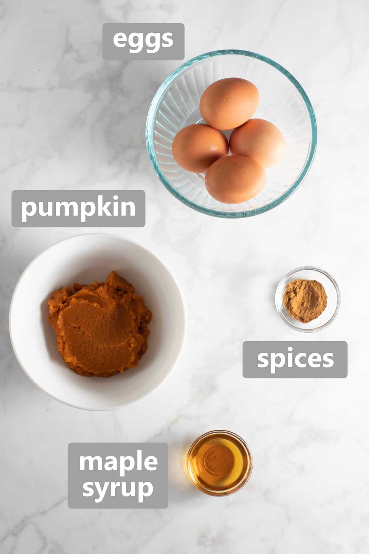 ingredients for pumpkin pancakes set out on marble background