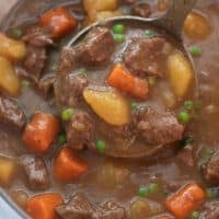 close up shot of beef stew being scooped with silver ladle
