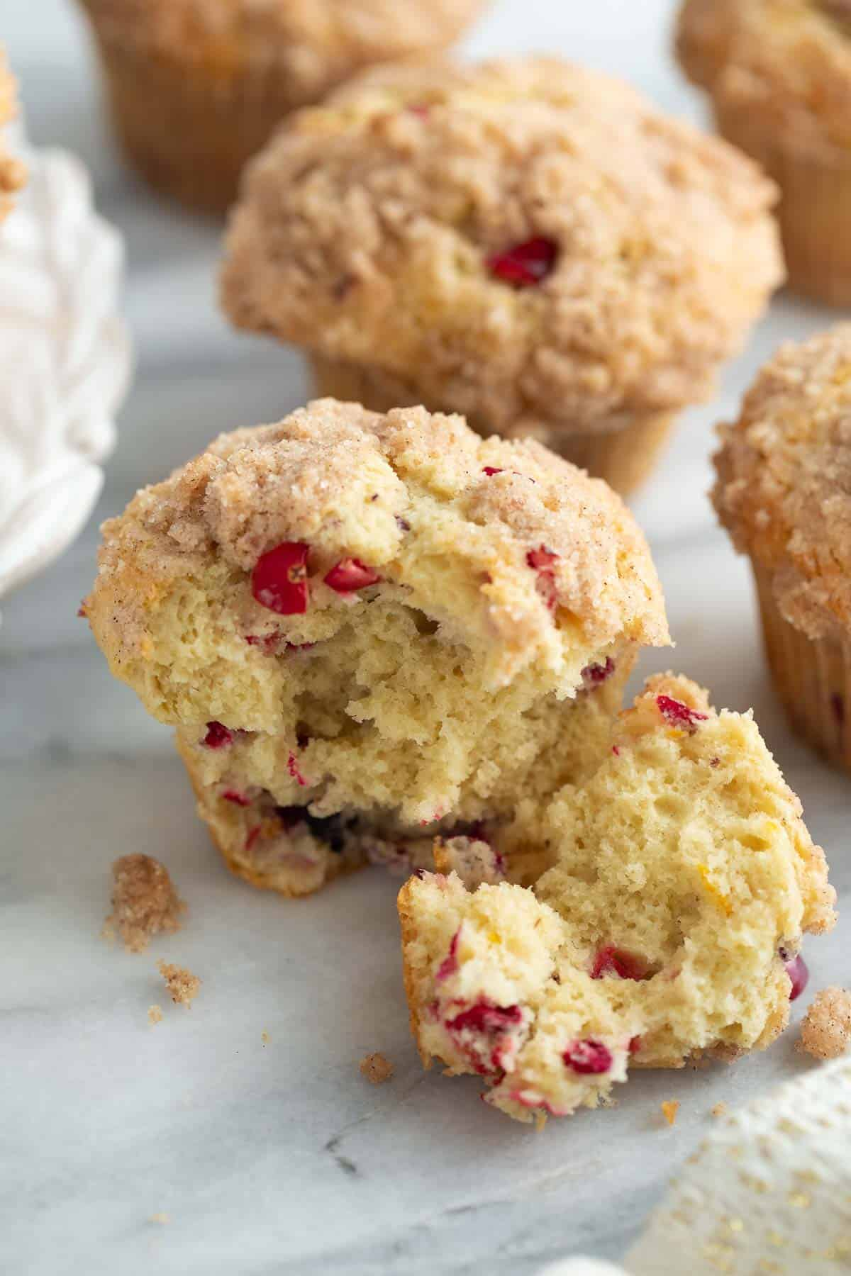 gluten free cranberry orange muffins with bite taken out of on marble background