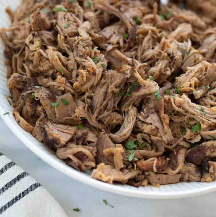 slow cooker pork in white bowl with silver spoon