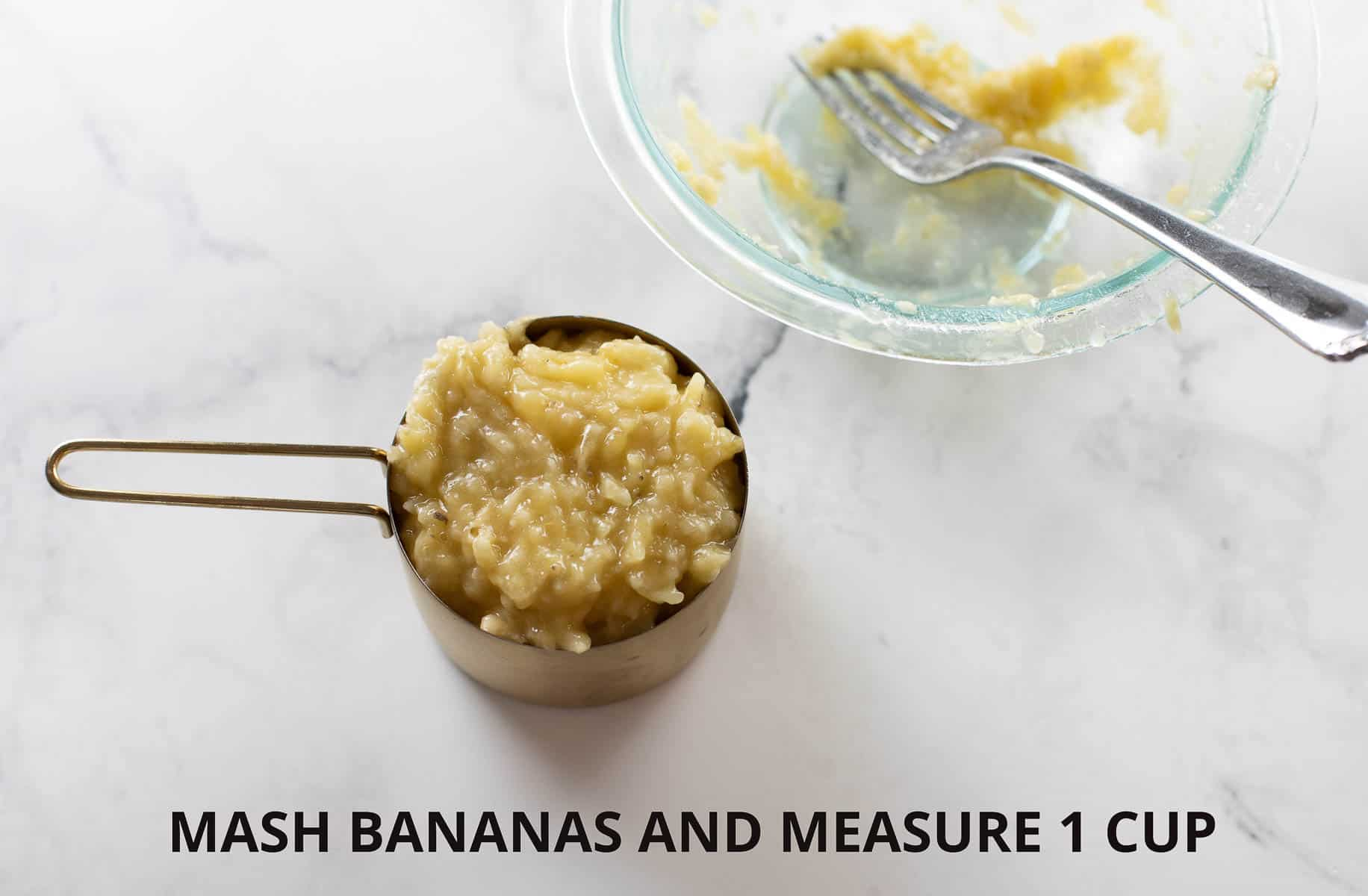mashed banana in gold measuring cup on marble background