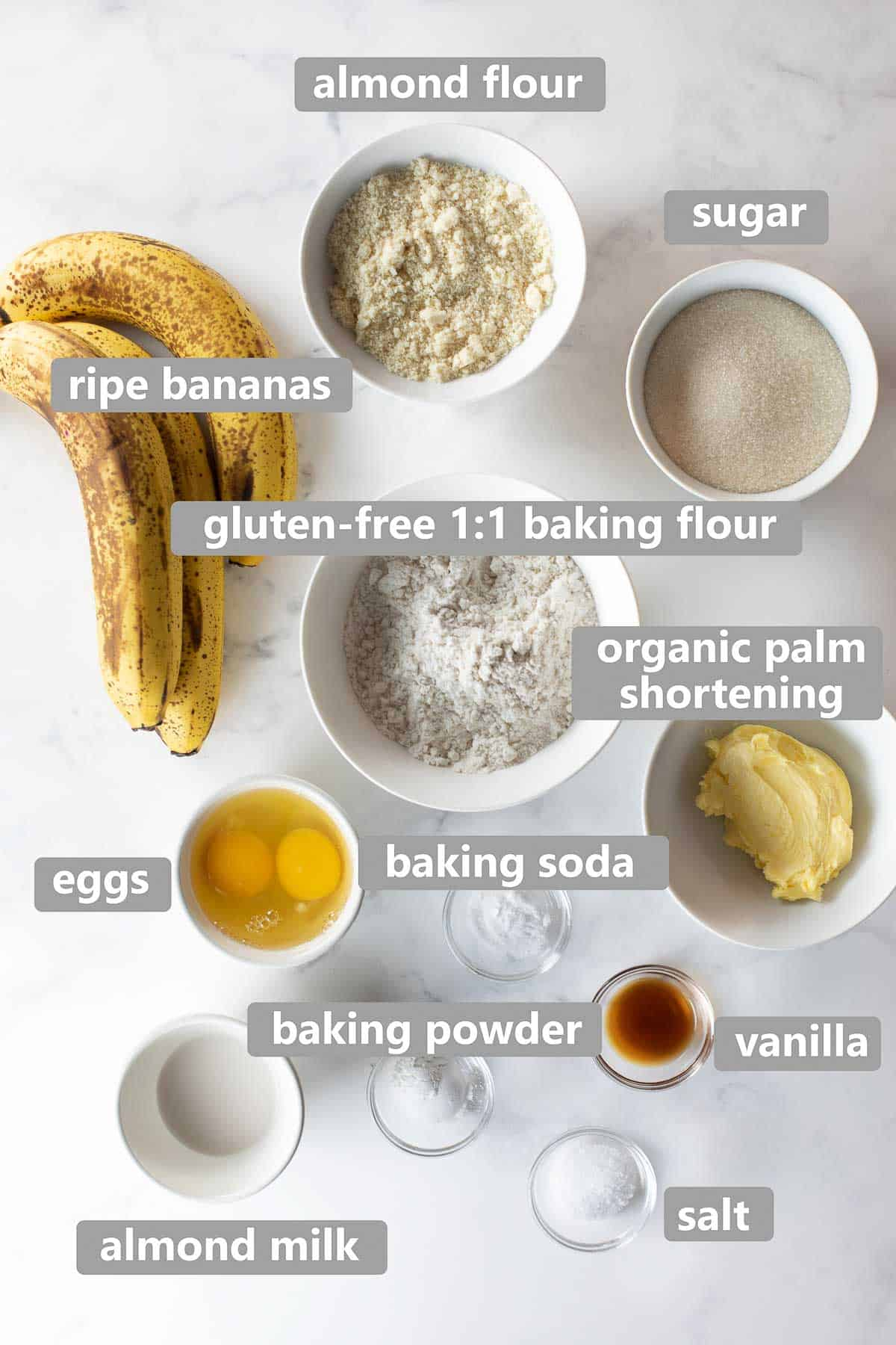 overhead shot of ingredients used to make gluten-free banana bread on marble background