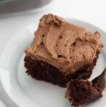 chocolate cake on white plate with fork taking bite