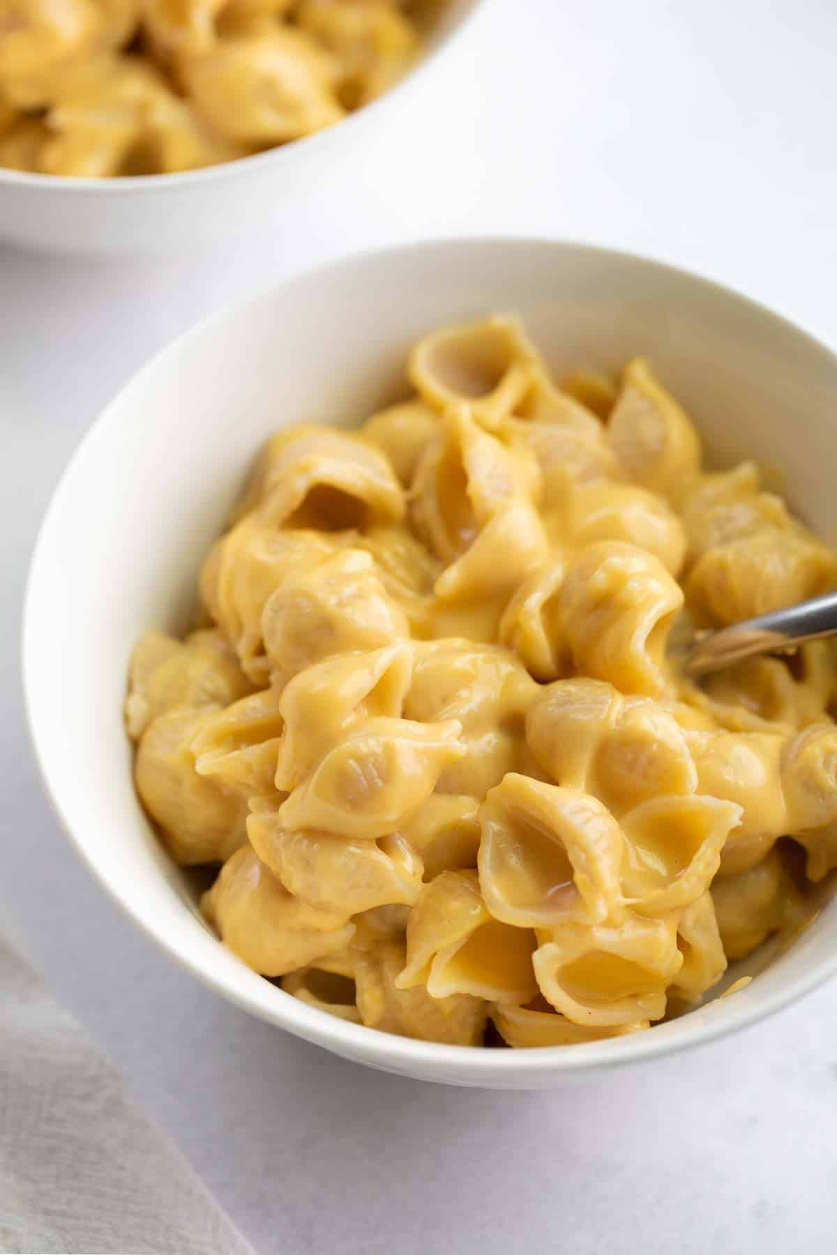close up shot of mac and cheese in white bowl with spoon