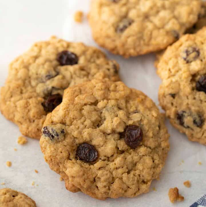 close up shot of gluten free oatmeal raisin cookies on white background with blue and white napkin