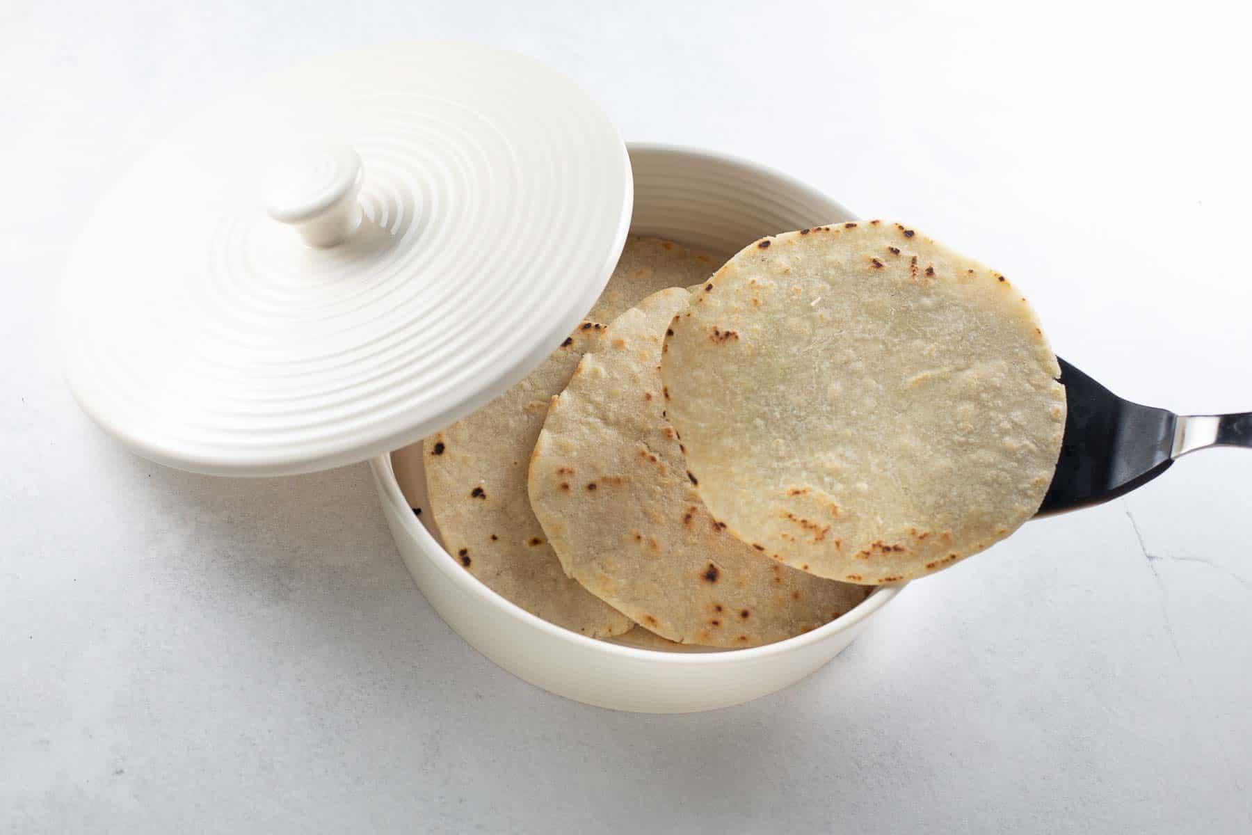 homemade gluten-free tortillas being placed in white warmer