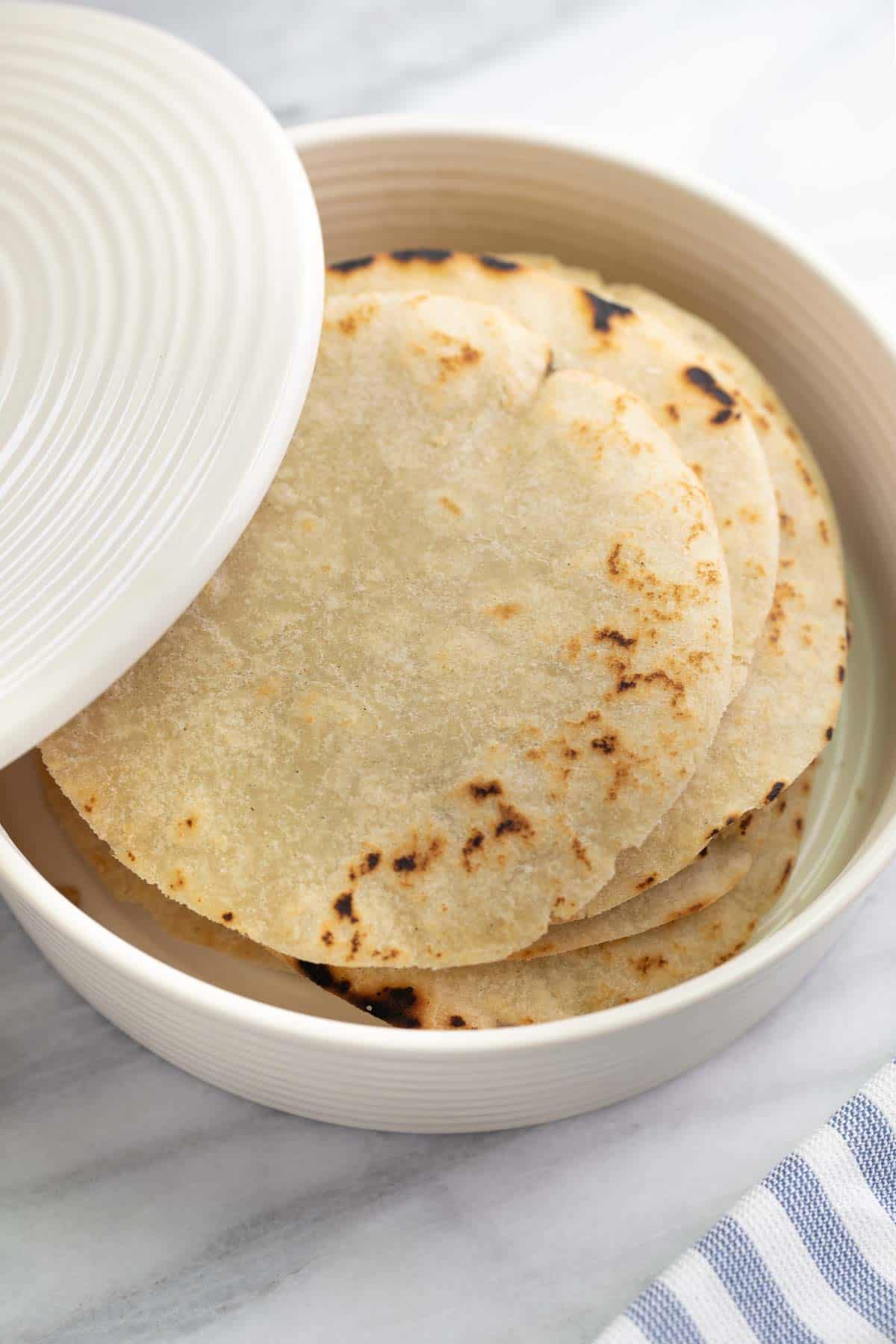 gluten free tortillas in white tortilla warmer on marble background