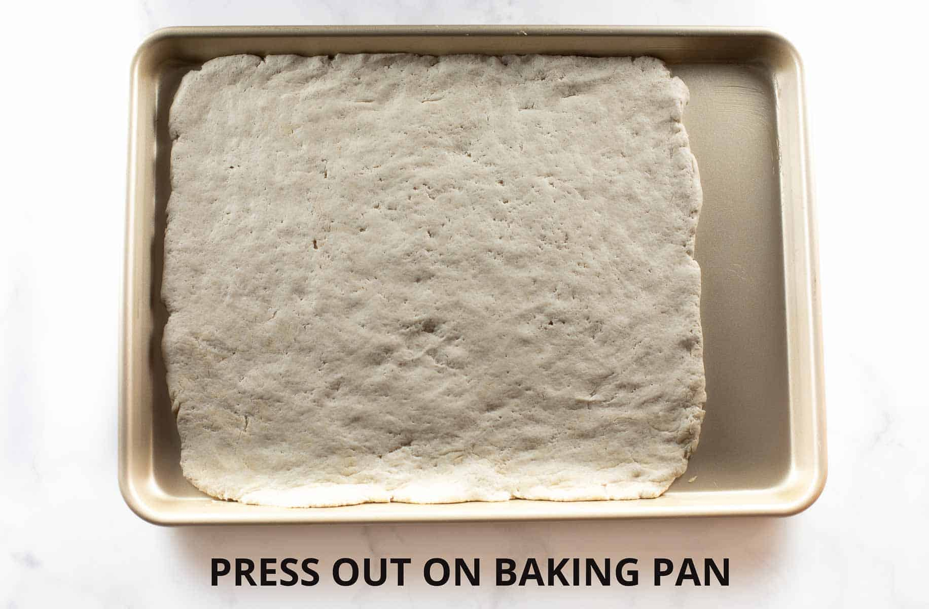 gluten free pizza dough pressed onto baking sheet