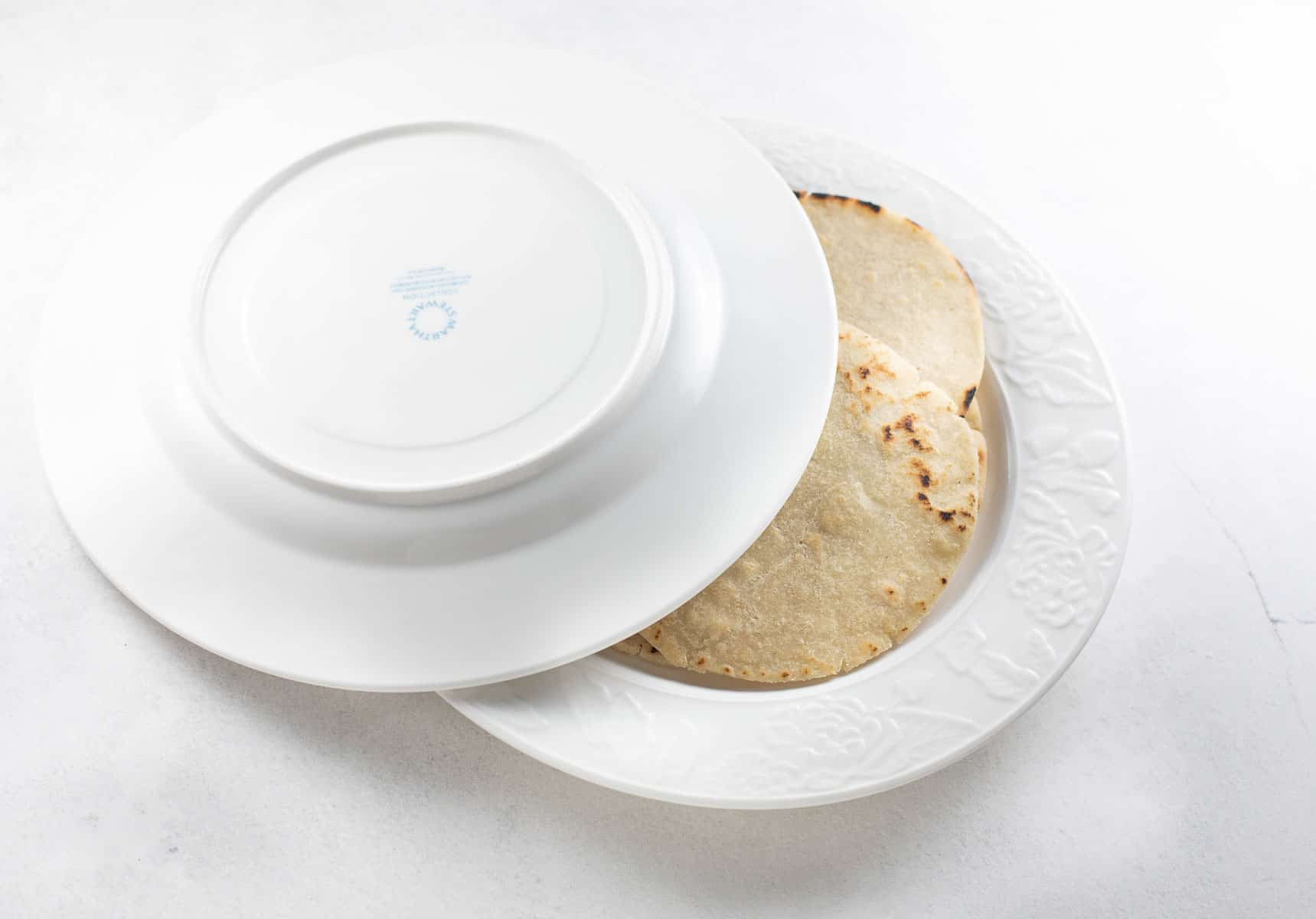 tortillas being placed in between 2 white plates to keep warm