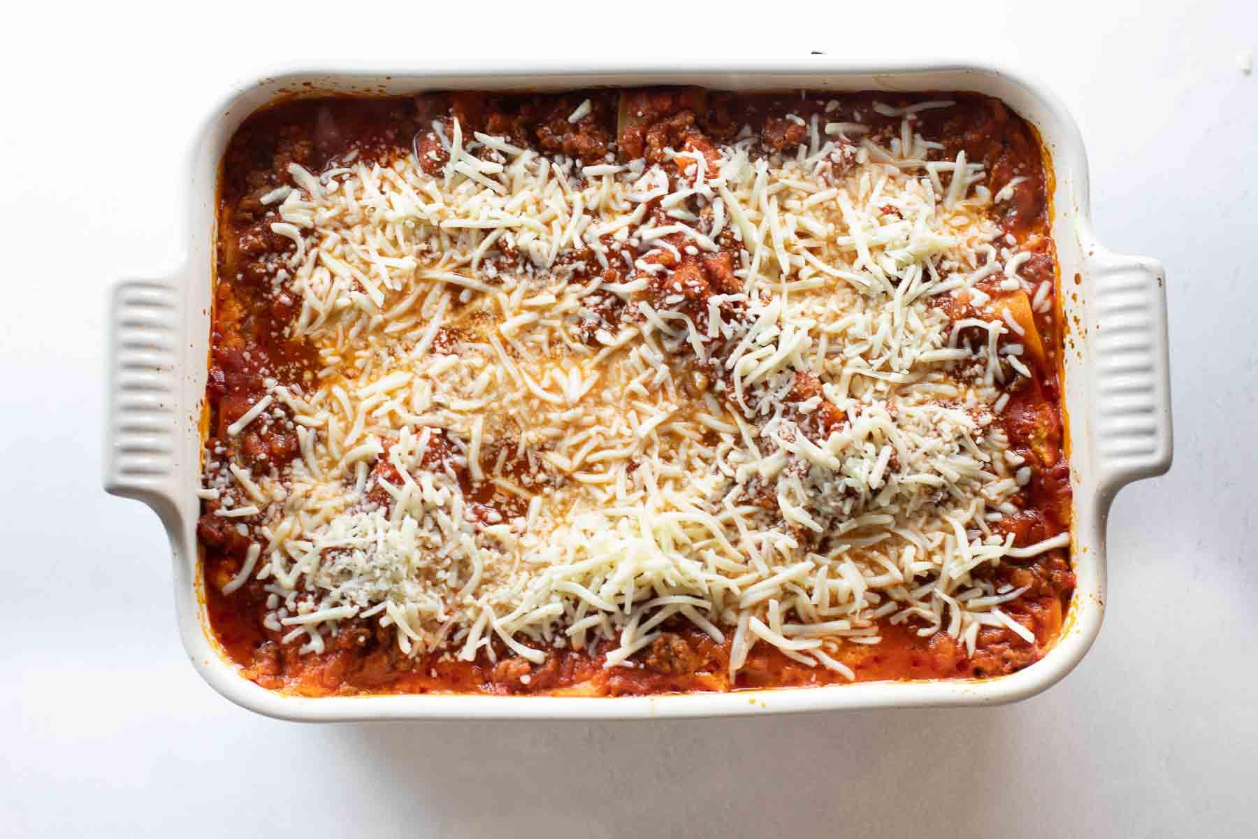 lasagna topped with mozzarella cheese in white baking dish