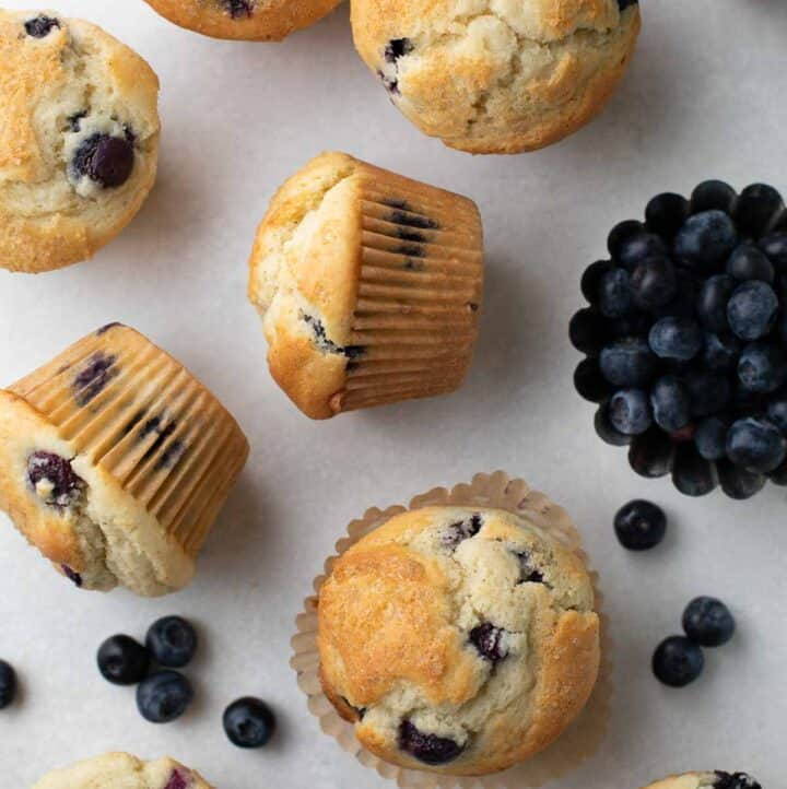 overhead shot of blueberry muffins on gray background topped with raw sugar