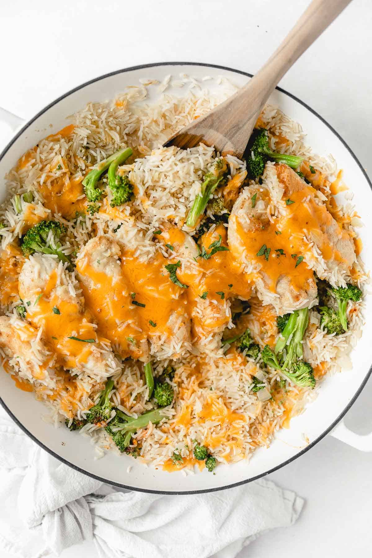 overhead shot of chicken broccoli rice with wooden spoon in white dish