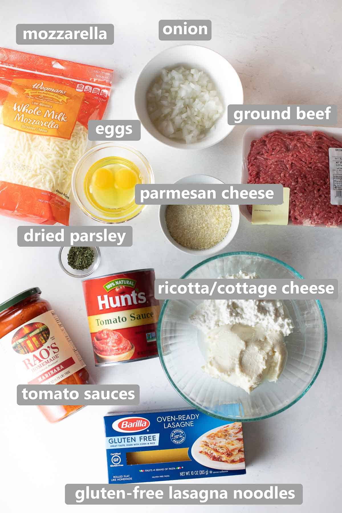 overhead shot of labeled ingredients to make gluten free lasagna on white background