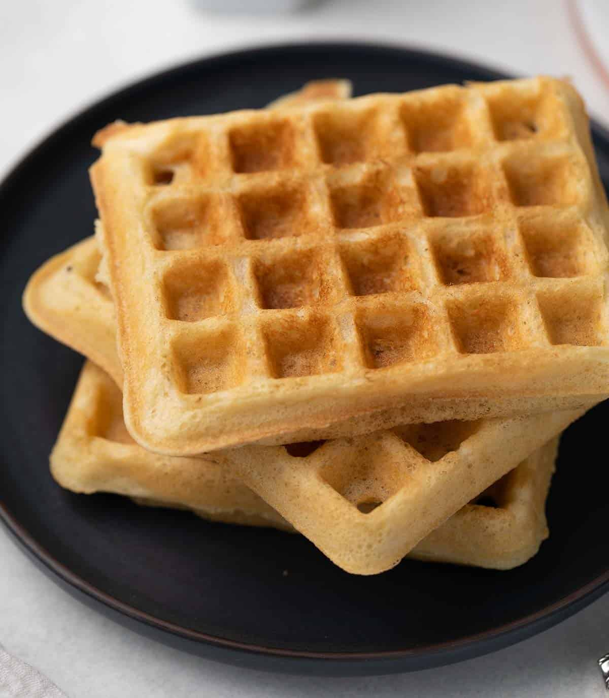waffles stacked on black plate before serving
