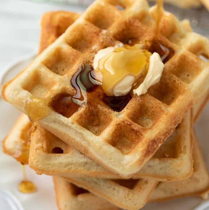 gluten free waffles on white plate with syrup being drizzled over
