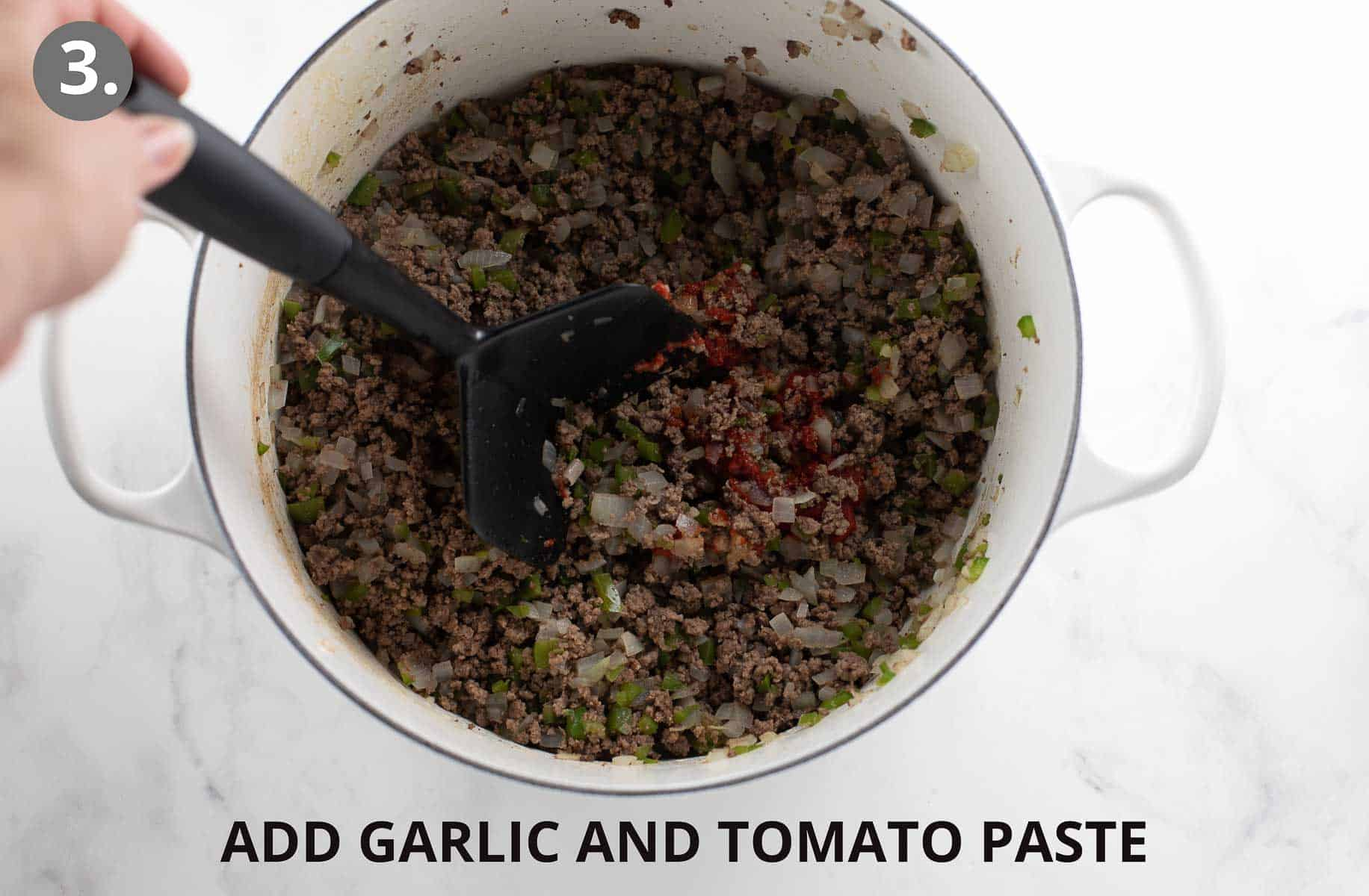 meat and peppers and onions cooking with garlic and tomato paster