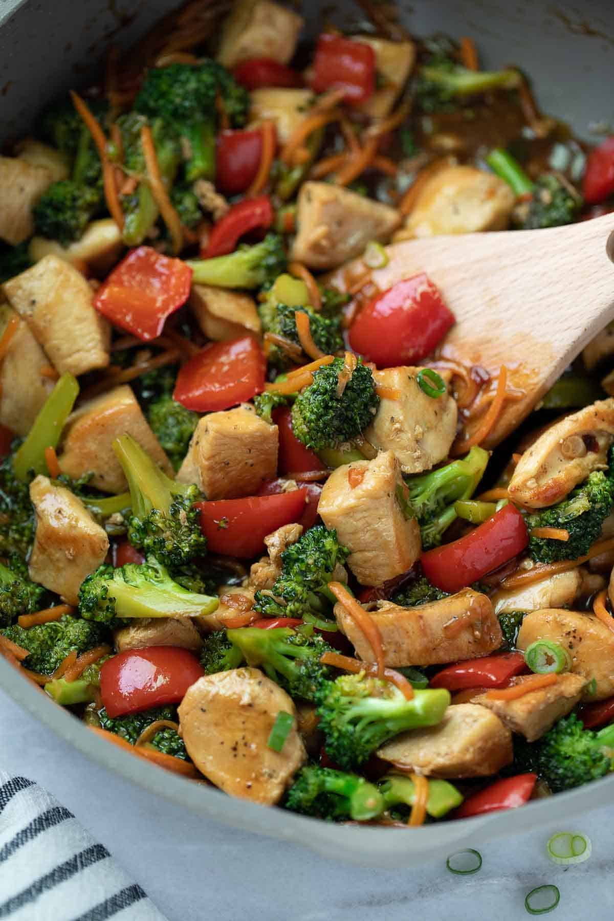 stir fry in skillet with wooden spoon