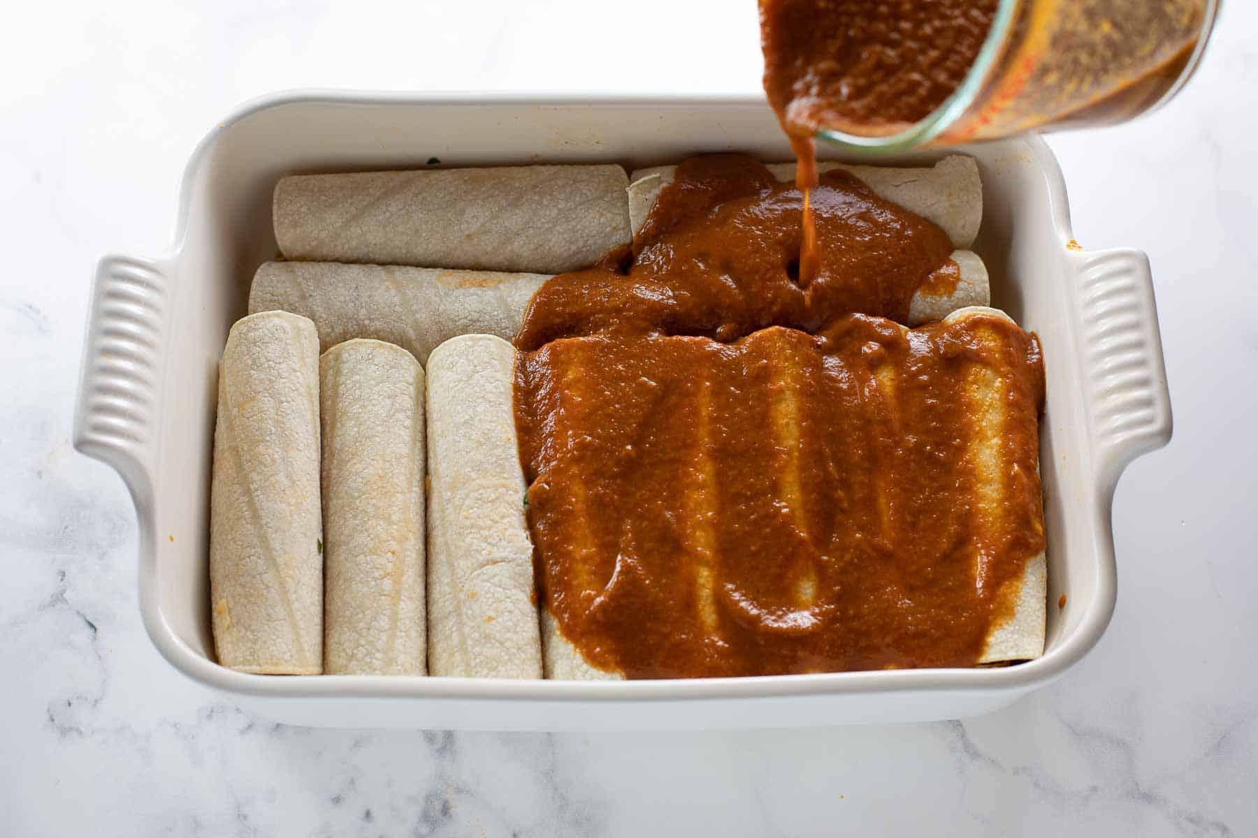 gluten free enchilada sauce being poured over chicken enchiladas