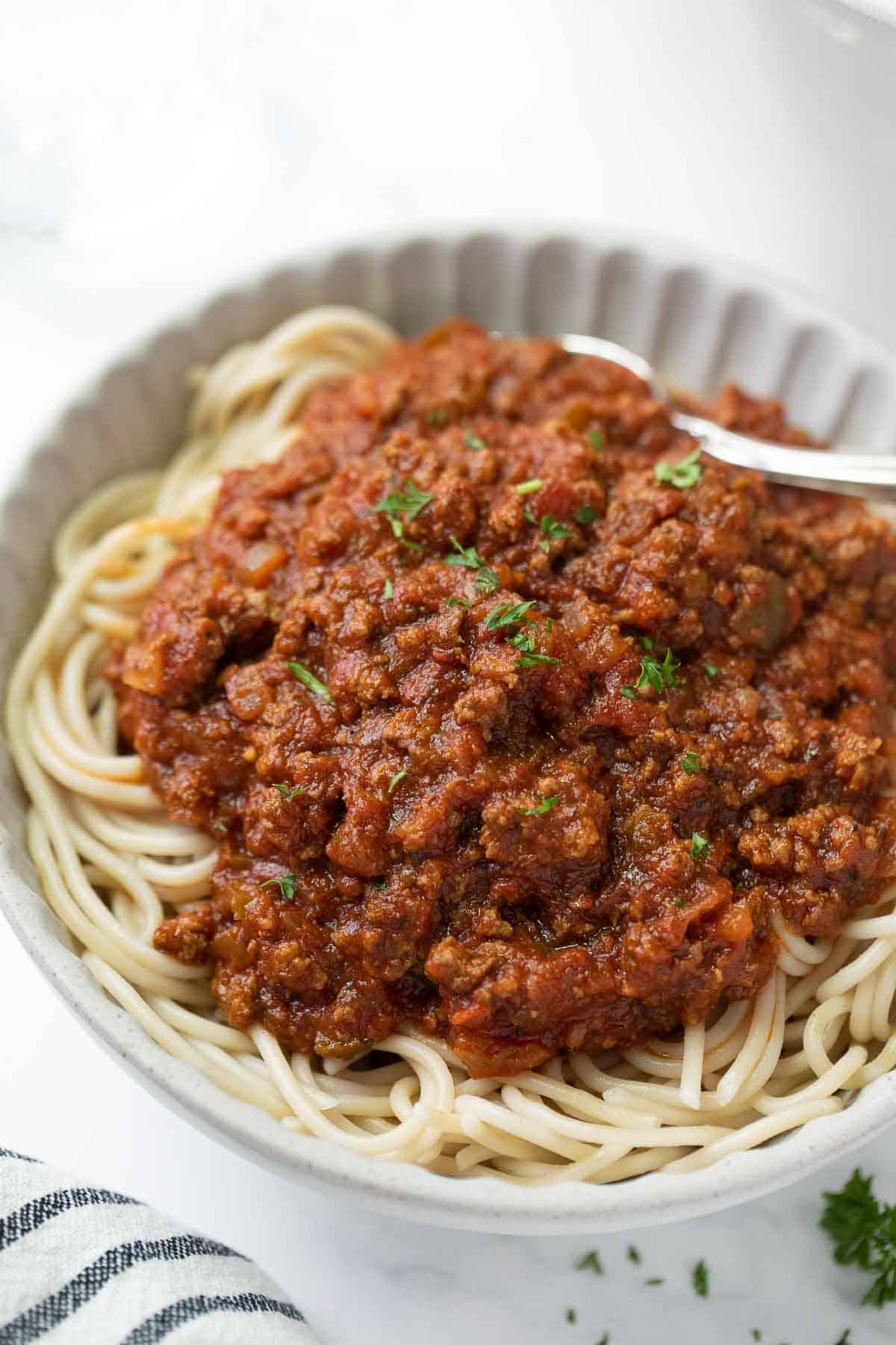 spaghetti sauce over cooked noodles in white plate