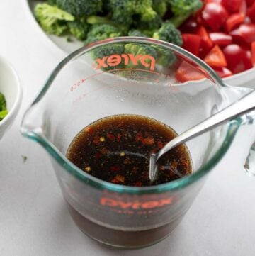 stir fry sauce whisked together in glass measuring cup