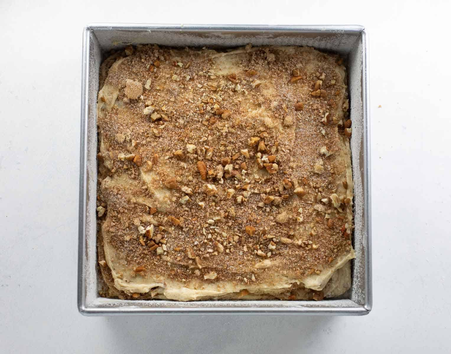coffee cake batter layered with cinnamon nut mixture in baking dish