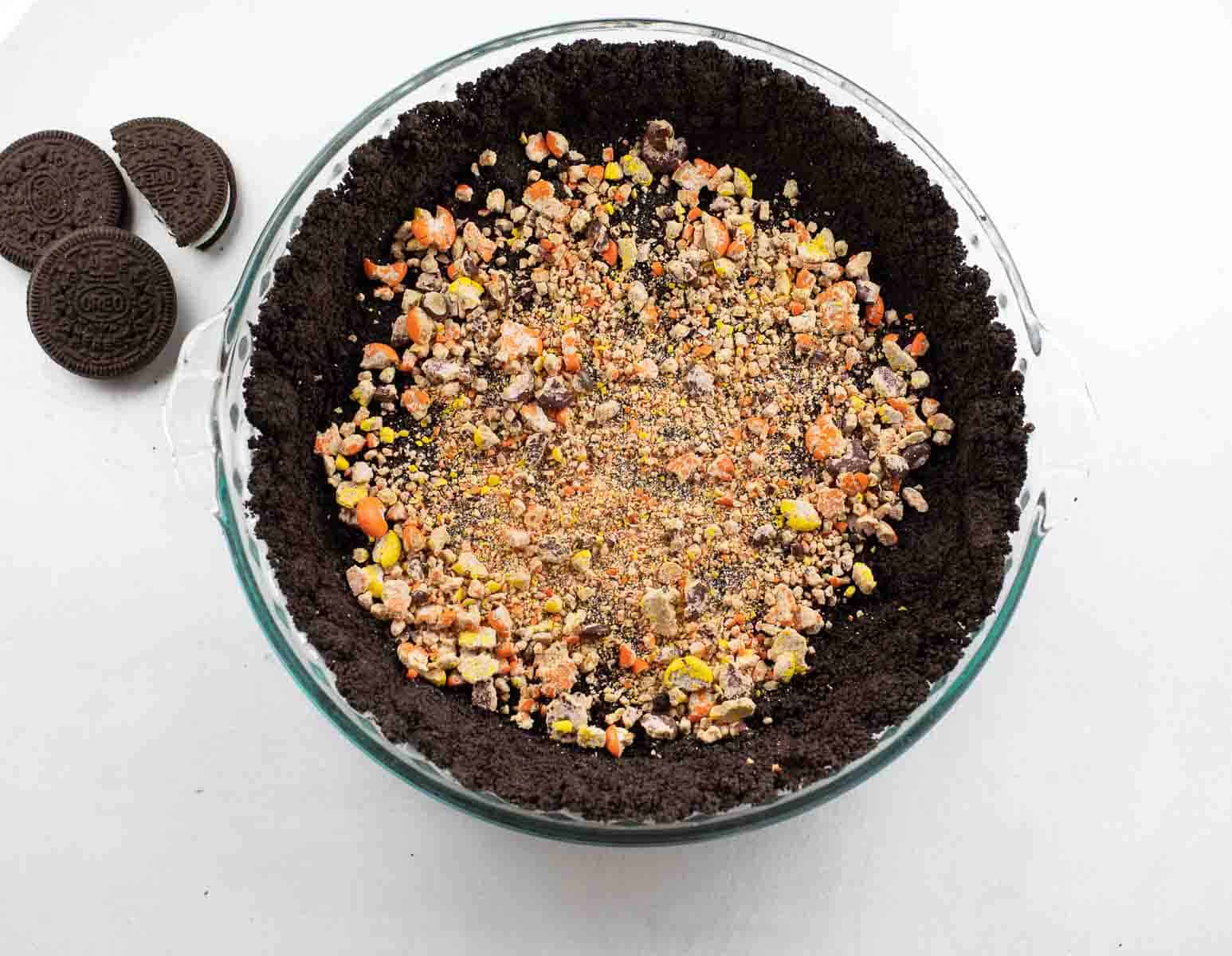 gluten free oreo crust sprinkled with Reese's pieces candy