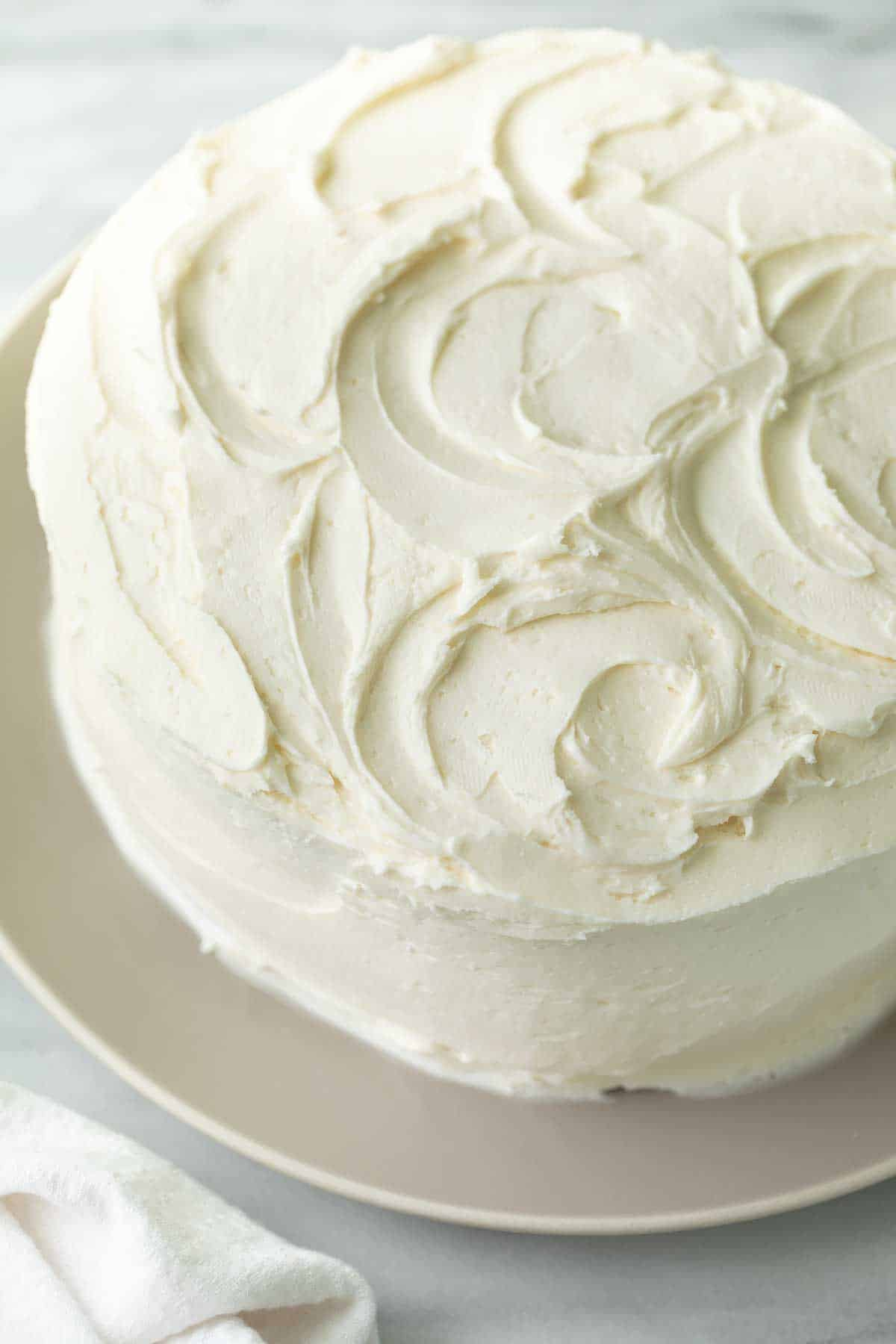 frosted gluten free cake with vanilla icing on gray plate