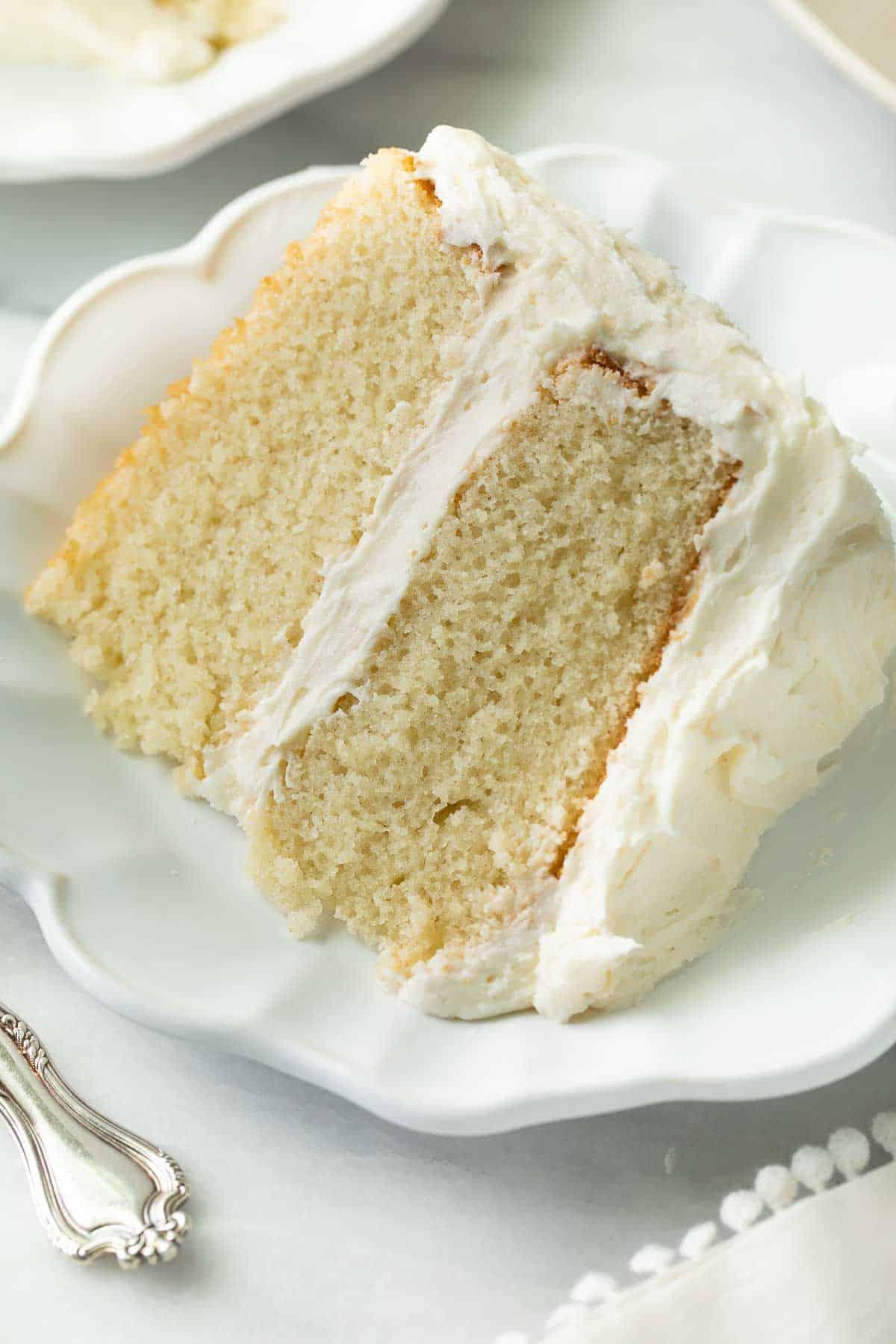 slice of gluten free vanilla cake on white plate