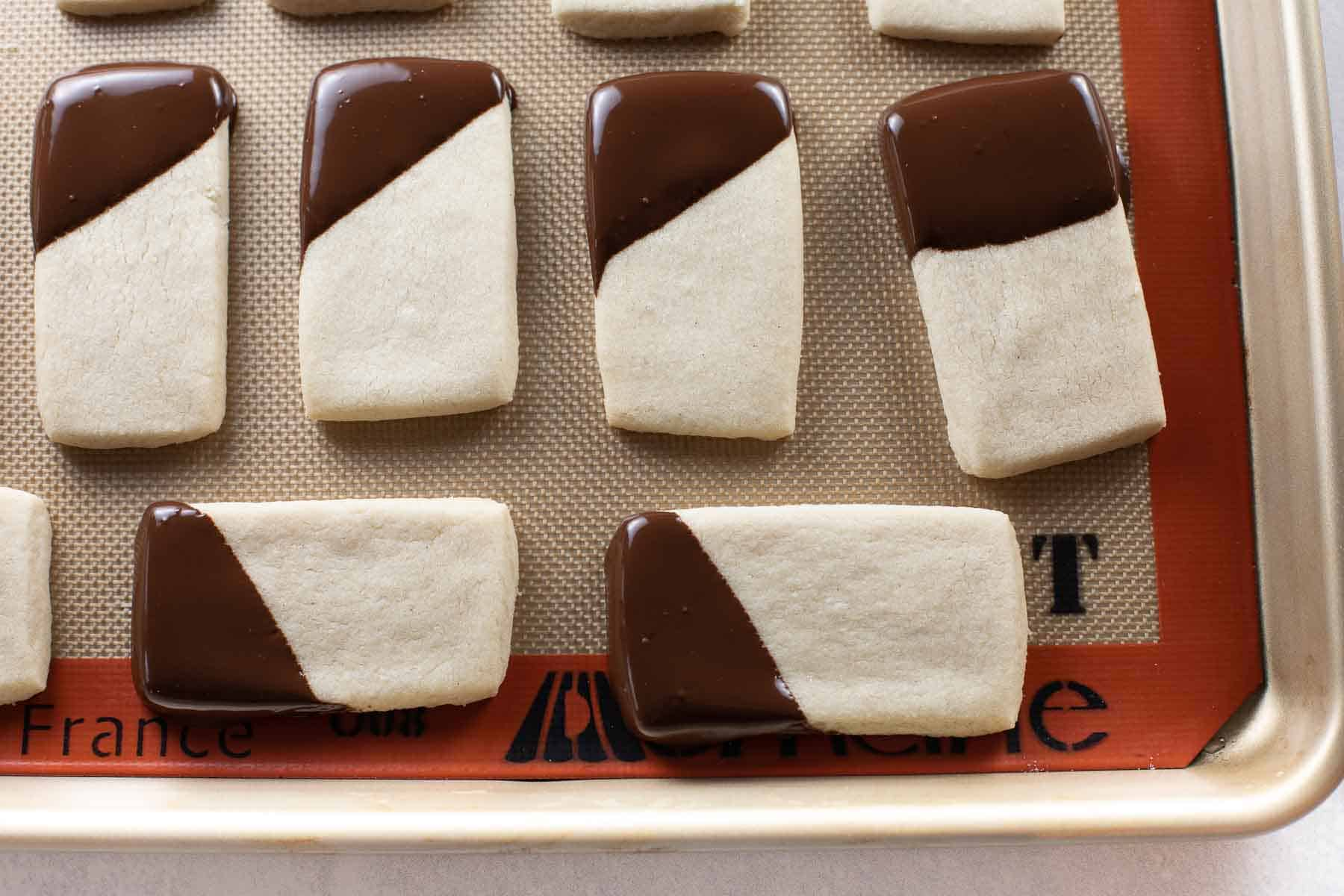 shortbread cookies dipped in chocolate on baking sheet