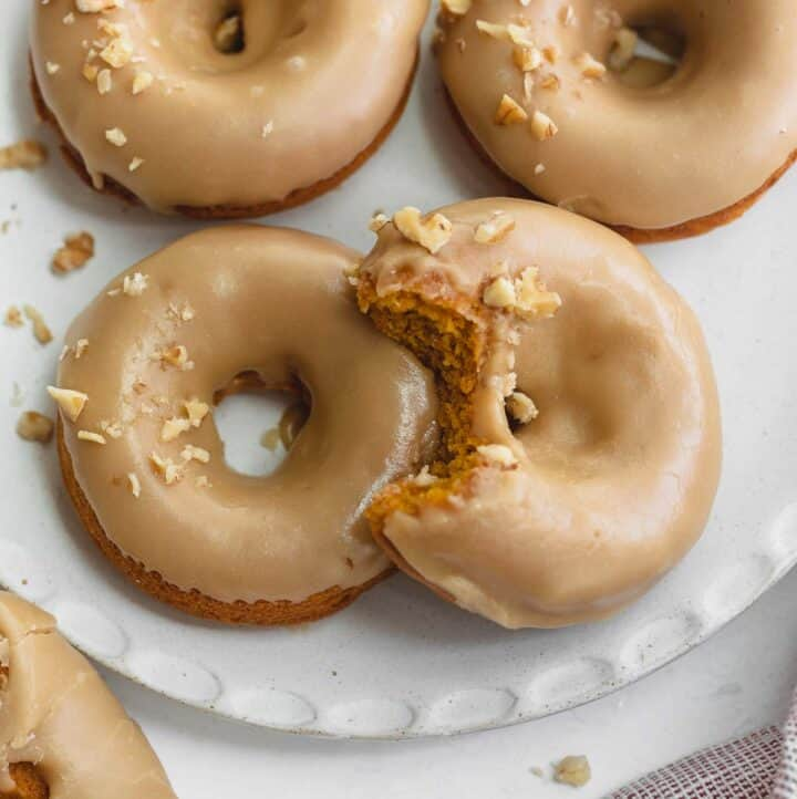 gluten free pumpkin donuts on white plate topped with walnuts
