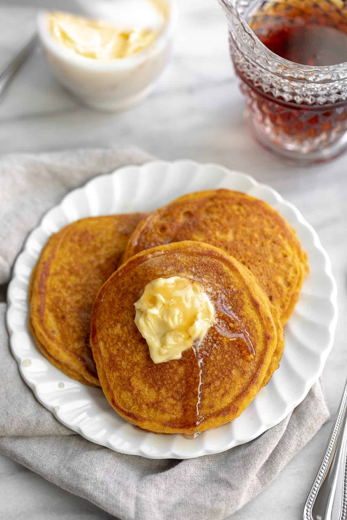 gluten free pumpkin pancakes on white plate topped with butter and syrup