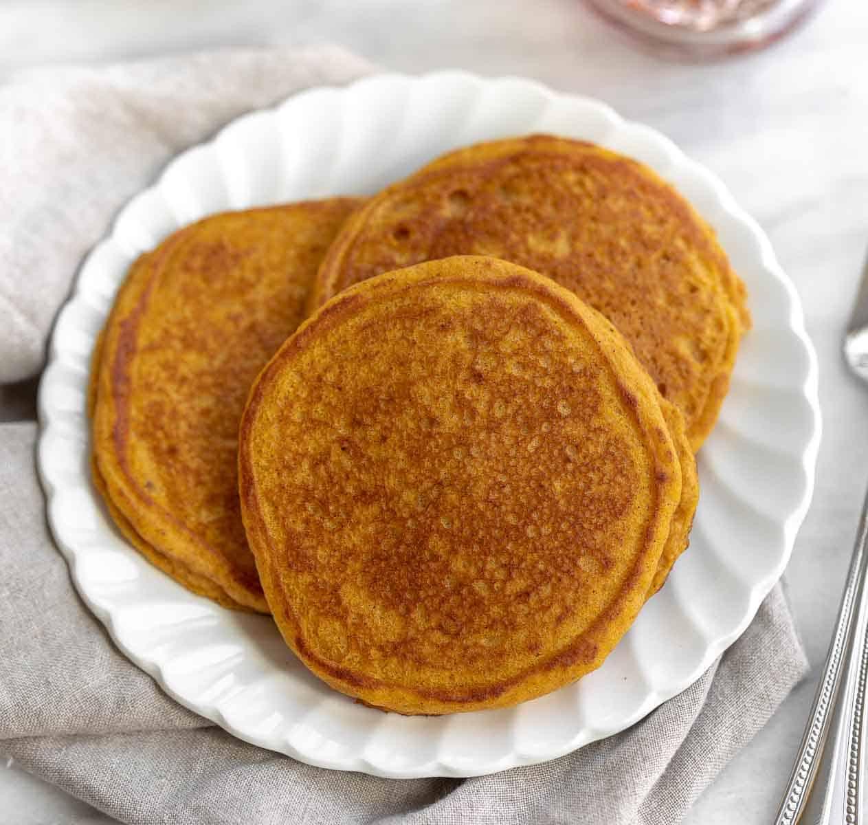gluten free pumpkin pancakes on white plate