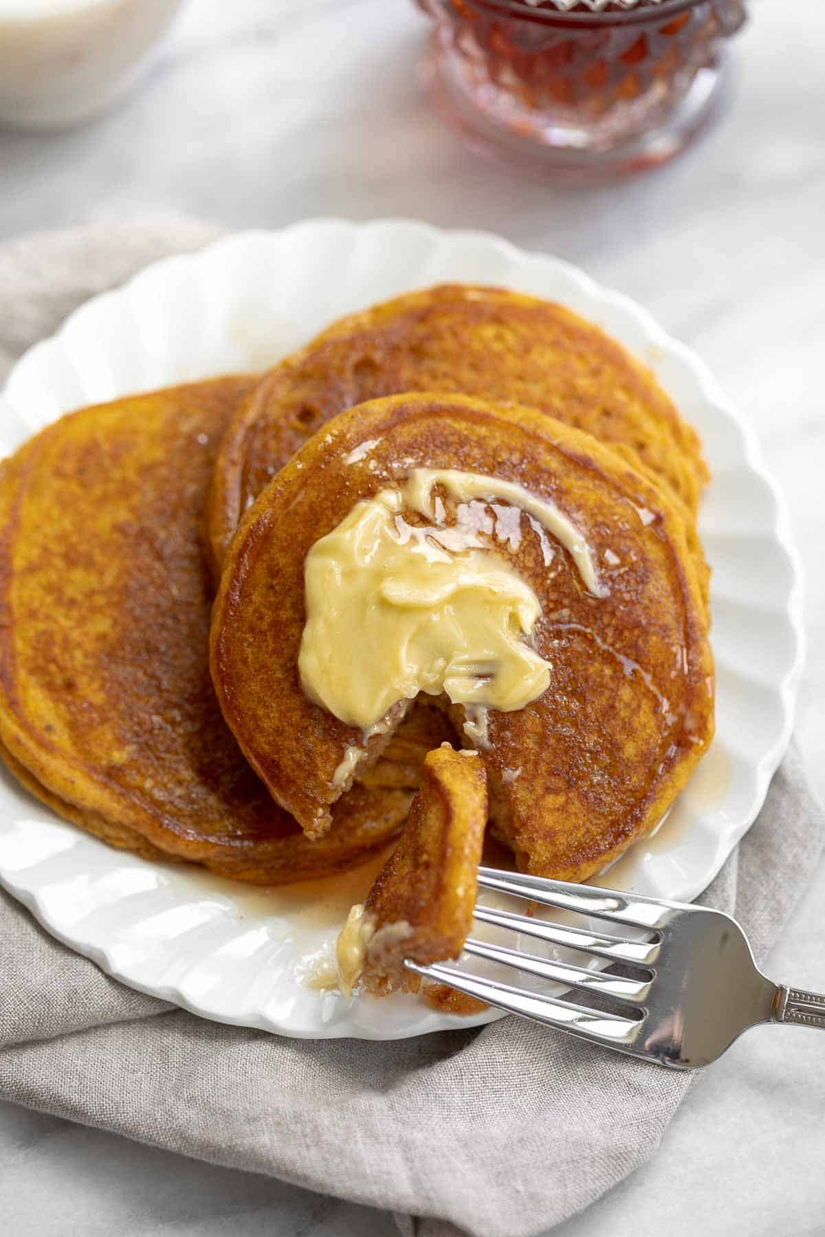 close up image of gluten free pumpkin pancakes on white plate topped with butter and syrup